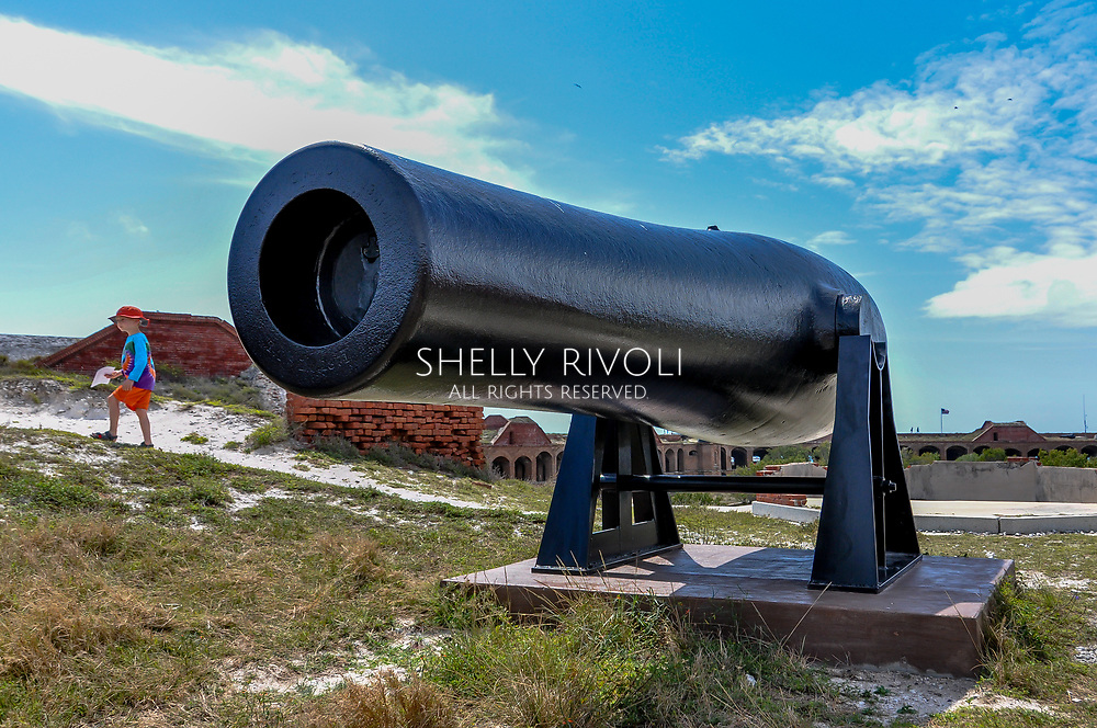 A young boy walks beside cannon on roof top of historic Fort Jefferson at Dry Tortugas National Park on a family day trip from Key West, Florida. Model released photo.