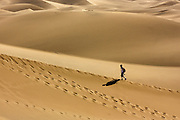 Lone hiker on sand dunes in Death Valley National Park, California