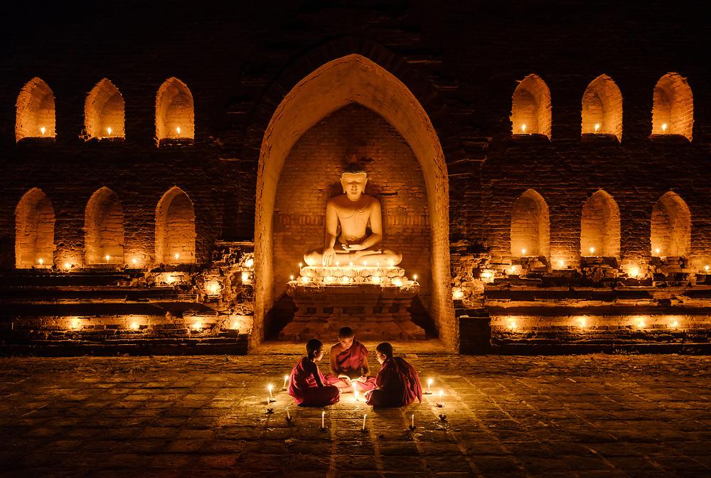 BAGAN, MYANMAR - CIRCA DECEMBER 2017: Monks seating around candelights on a temple in Bagan