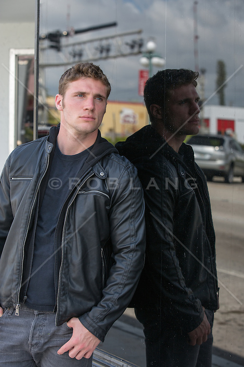 rugged handsome man in a black tee shirt and leather jacket outdoors