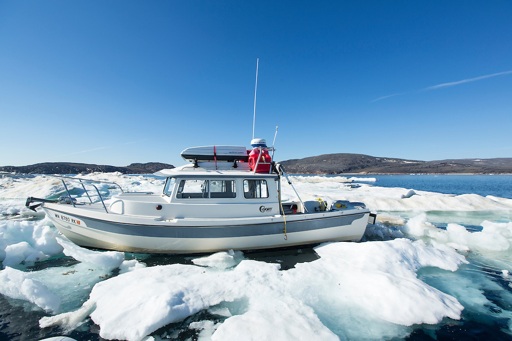 Canada, Nunavut Territory, C-Dory expedition boat caught in sea ice in Frozen Strait near White Island on summer morning