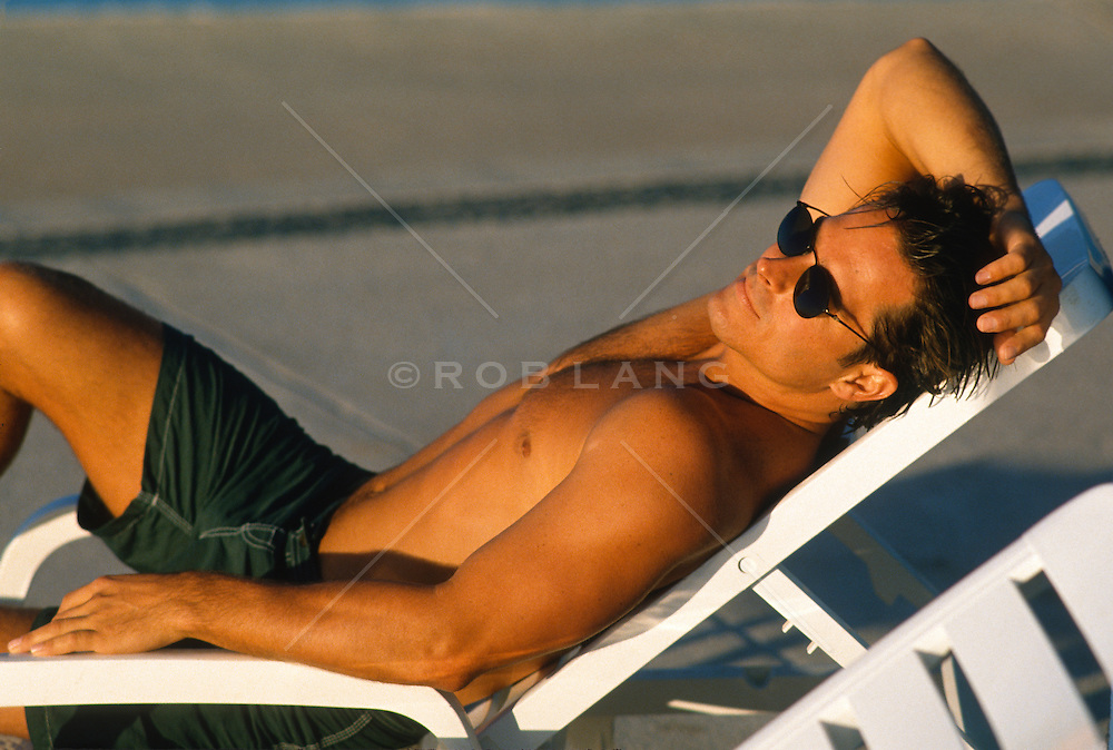 Shirtless toned man lounging on a chair in the sun