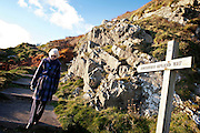 Older lady walking past Southern Upland Way trail sign next to steps and rocks.