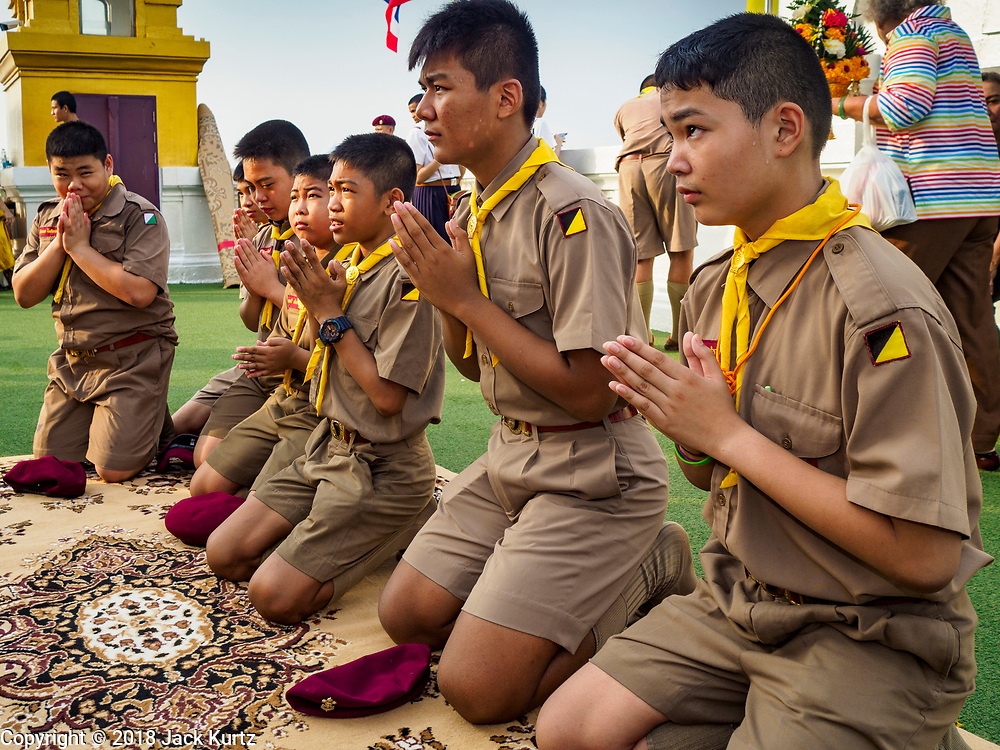 15 NOVEMBER 2018 - BANGKOK, THAILAND: Thai Boy Scouts pray during the red cloth ceremony at Wat Saket, also called the Golden Mount. Wat Saket is on a man-made hill in the historic section of Bangkok. The temple has golden spire that is 260 feet high, which was the highest point in Bangkok for more than 100 years. The temple construction began in the 1800s during the reign of King Rama III and was completed in the reign of King Rama IV. A  red cloth (reminiscent of a monk's robe) is placed around the chedi at the top of  Golden Mount during the weeks leading up to the Thai holy day of Loy Krathong, which is November 22 this year.     PHOTO BY JACK KURTZ