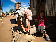 03 AUGUST 2015 - SANKHU, NEPAL: A man and his son repair the doors to their home in Sankhu, a community about 90 minutes from central Kathmandu. He is a farmer who works on his home when he has time in between tending to his fields. His family is living in the home while they work on it. The Nepal Earthquake on April 25, 2015, (also known as the Gorkha earthquake) killed more than 9,000 people and injured more than 23,000. It had a magnitude of 7.8. The epicenter was east of the district of Lamjung, and its hypocenter was at a depth of approximately 15 km (9.3 mi). It was the worst natural disaster to strike Nepal since the 1934 Nepal–Bihar earthquake. The earthquake triggered an avalanche on Mount Everest, killing at least 19. The earthquake also set off an avalanche in the Langtang valley, where 250 people were reported missing. Hundreds of thousands of people were made homeless with entire villages flattened across many districts of the country. Centuries-old buildings were destroyed at UNESCO World Heritage sites in the Kathmandu Valley, including some at the Kathmandu Durbar Square, the Patan Durbar Squar, the Bhaktapur Durbar Square, the Changu Narayan Temple and the Swayambhunath Stupa. Geophysicists and other experts had warned for decades that Nepal was vulnerable to a deadly earthquake, particularly because of its geology, urbanization, and architecture.    PHOTO BY JACK KURTZ