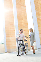 Businesspeople with bicycle conversing outside building