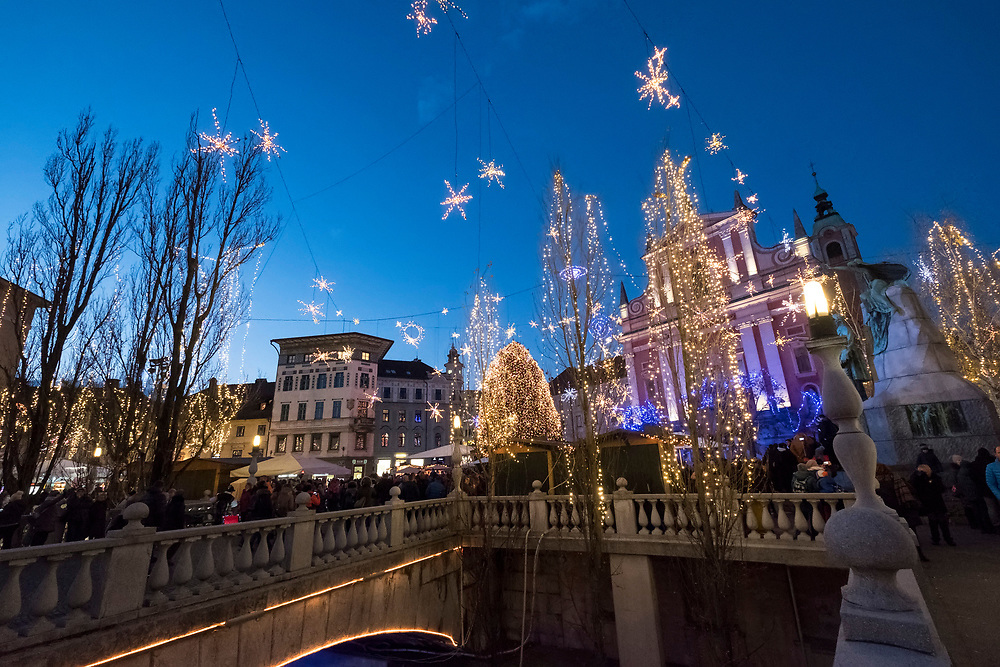 LJUBLJANA, SLOVENIA - DECEMBER 02:  Locals and tourists cross the Triple Bridge on December 2, 2017 in Ljubljana, Slovenia. The traditional Christmas market and lights will stay until 1st week of January 2018.  (Photo by Marco Secchi/Getty Images)