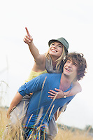 Cheerful woman showing something while enjoying piggyback ride on man in field
