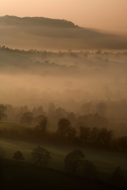 View along the limestone Cotswold escarpment and misty countryside at dusk, Coaley Peak, Gloucestershire, UK