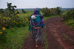 Fifteen-year-old Destaye walks with her son near Bahir Dar, Ethiopia on Aug. 9, 2012. Destaye and her husband Addisu, 27, divide their time between working in the fields and taking care of their 6-month-old baby. Like many other young couples, they tend to the domestic, economic and personal demands of being young parents. At the time of their marriage, when Destaye was age 11, she was still in school and her husband expressed interest in letting her continue her education. Since the birth of their son, however, she has had to confine her life exclusively to being a wife and mother.