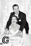 Black and white photo of a bride and groom laughing during their wedding toasts -- The wedding took place at The Genessee Grande Hotel in Syracuse, NY