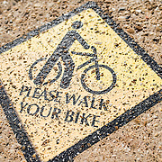 "A ""Please Walk Your Bike"" caution sign pained on the sidewalk in Washington DC in an area that features heavy pedestrian traffic."