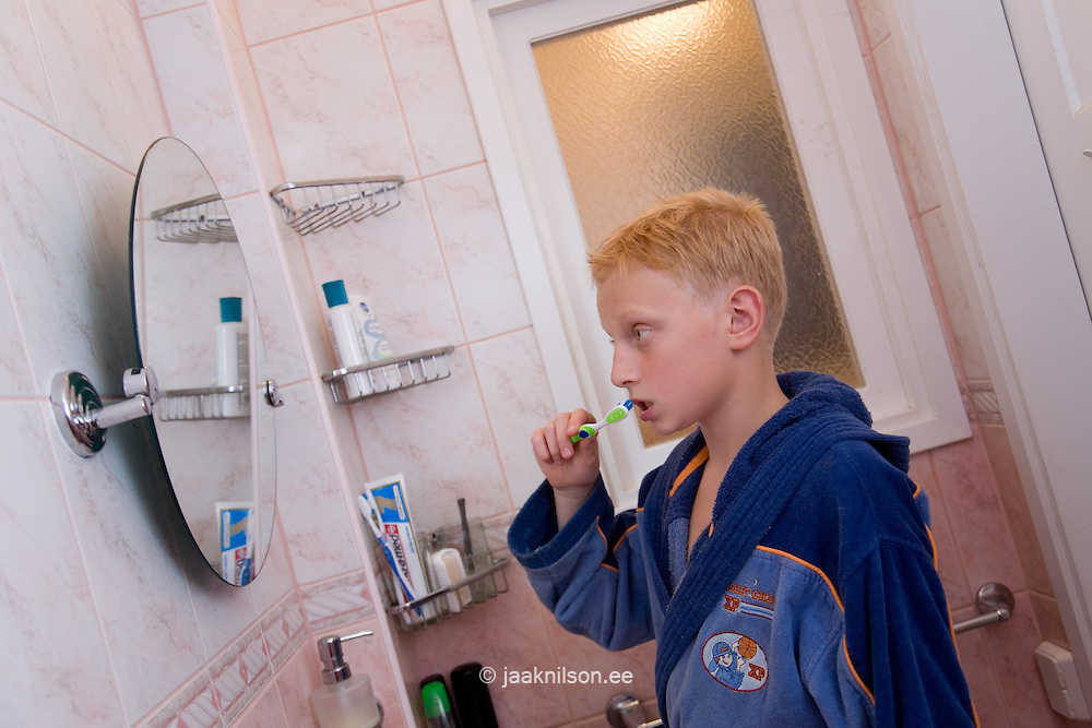 Teenage Boy Brushing Teeth in Bathroom