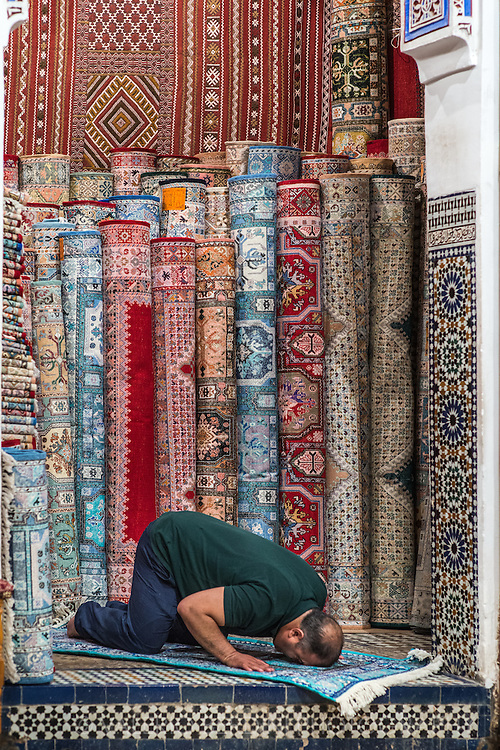 The owner of a carpet cooperative in Fez, Morocco, uses one of his rugs to take a break off his trade to abide one of the 5 prayers muslim people must commit everyday.