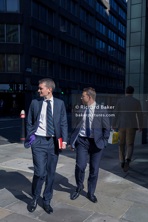 Two businessmen look over their shoulders on Fenchurch Street in the City of London - the capital's financial centre (aka The Square Mile), on 27th September 2018, in London, England.