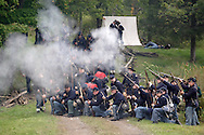 Members of the 124th New York State Volunteers fire on a Confederate position during a Civil War reenactment at the Orange County Farmers Museum on Sept. 23, 2006.