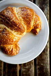 Golden brown flakey croissant on a white plate