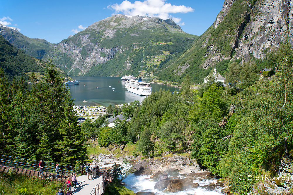 Tourists walking along a walkway next to the Geiranger waterfall and large cruise ships on Geiranger Fjord, Vestlandet, Norway