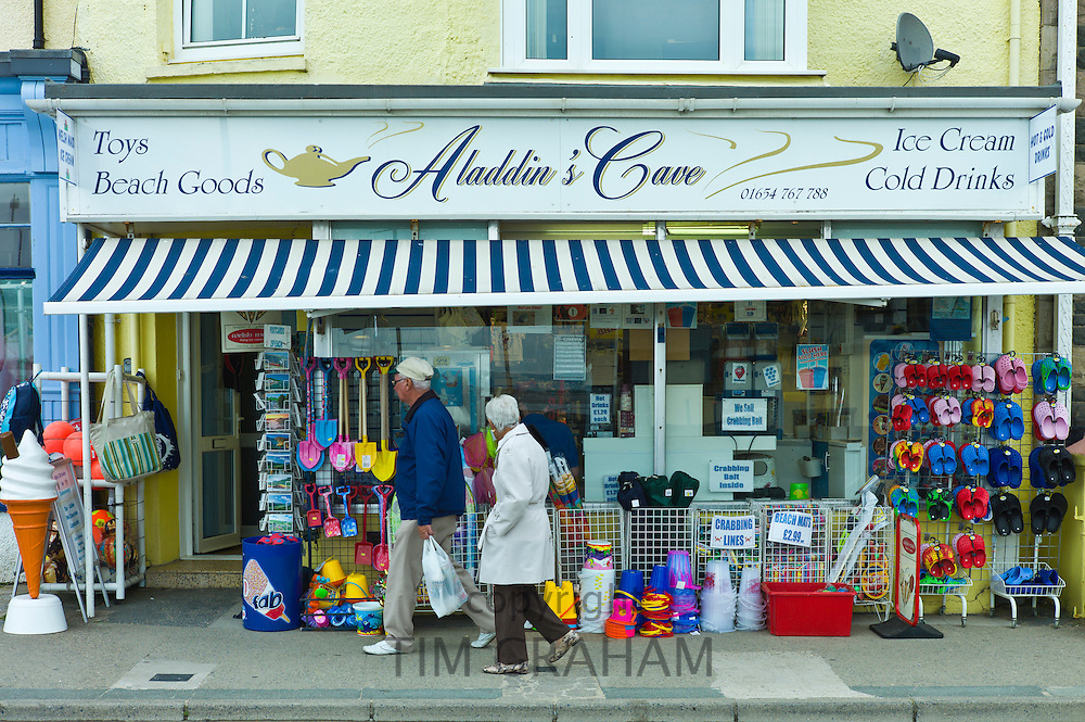 Retired couple pass Aladdin's Cave store selling seaside products in Aberdyfi, Aberdovey, Snowdonia, Wales