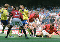 Dennis Bergkamp (Arsenal) evades two tackles from Roy Keane and Nicky Butt (Utd). Manchester United v Arsenal. Community Shield.10/8/03. Millennium Stadium. Credit : Colorsport/Andrew Cowie.