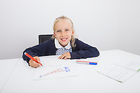 Portrait of happy girl drawing on paper at table