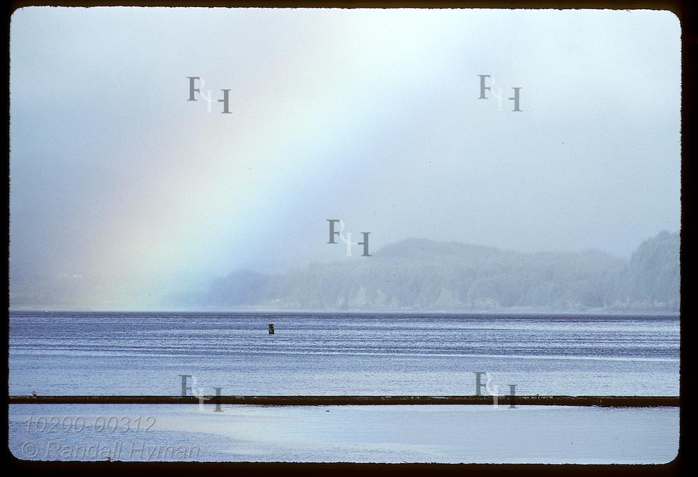 Rainbow soars skyward over Chiniak Bay as storm clears on a July morning at Kodiak Island. Alaska