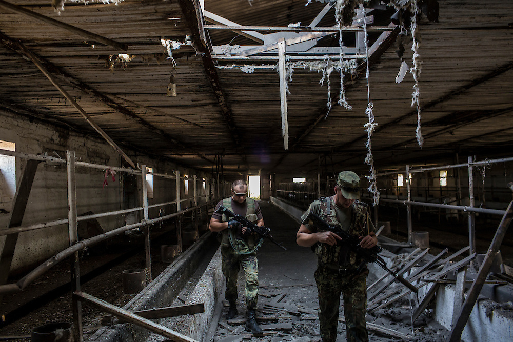 CHERMALYK, UKRAINE - AUGUST 29, 2015: Two Ukrainian soldiers walk inside a farm building that was hit by a shell, creating the hole overhead, two days earlier in Chermalyk, Ukraine. The farm was shelled by rebels based just across the nearby Kalmius River, with a level of skill that the soldiers felt indicated they were being targeted by professional Russian soldiers rather than rebel irregulars. CREDIT: Brendan Hoffman for The New York Times