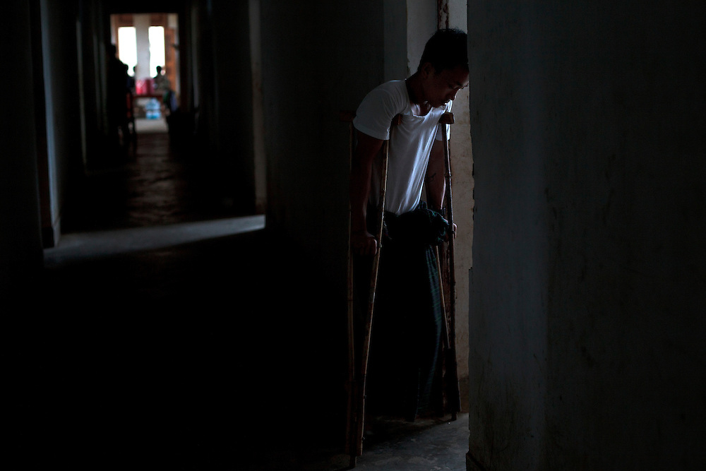 Kachin's militia member Lalaw Ze Dai, from Waimaw village, 25, try to walk with his crutches in the General Military Hospital in Laiza village close to the China border, Myanmar on July 26, 2012. He was injured by a landmine in June, 26, 2012 loosing part of his right leg on top of knee.