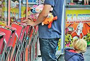 Nederland, Groesbeek, 2-9-2017Een kleine dorpskermis. Het gaat niet goed met de kleine kermissen. Het bezoek loopt terug. Een man speelt aan een gokkast, de hijskraantjes, terwijl zijn kind achter hem staat. Hij heeft al een knuffel gewonnen.Foto: Flip Franssen