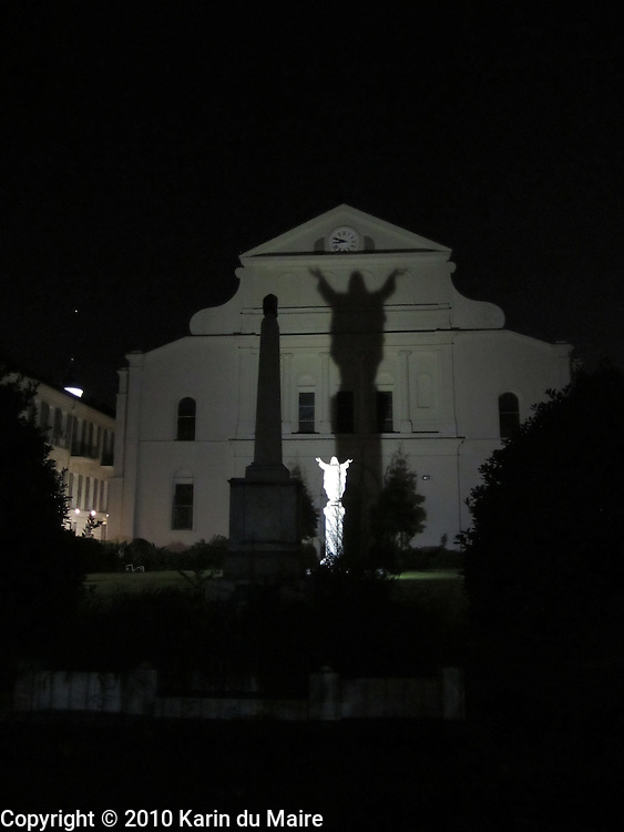 St. Anthony's Garden behind St. Louis Cathedral in New Orleans, Louisiana. Imposing shadow from the statue of Jesus Christ onto the cathedral at nighttime!