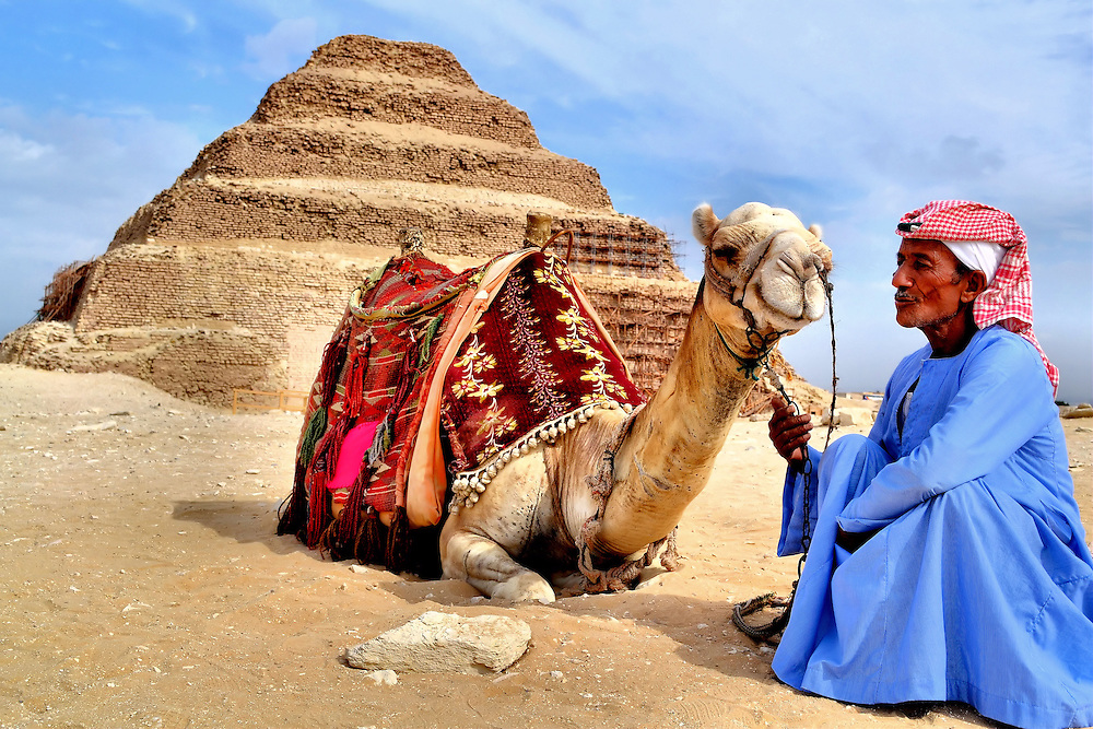 Camel and Egyptian Man at Step Pyramid Cairo, Egypt<br /> The Step Pyramid of King Djoser at Saqqara was built around 2,650 BC. It is considered to be Egypt&rsquo;s first pyramid. The ancient structure is over 200 feet tall and consists of six external levels. Underground it is more impressive. There is a network of chambers, tunnels and galleries traversing over three miles. This camel seems to be smiling with pride. Or was he puckering up for a kiss from his Egyptian owner?