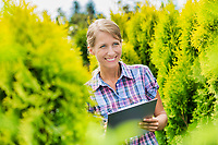 Portrait of mature woman writing report on clipboard over plants growing in the garden