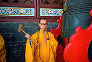 Buddist monk ringing the Huating Temple gong, China