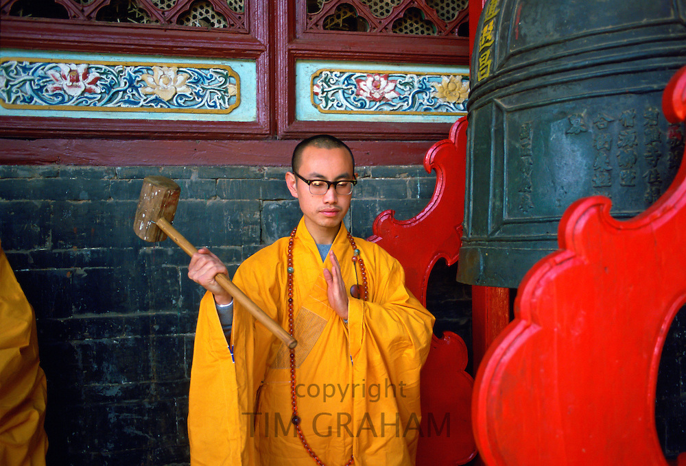 Buddist monk ringing the Huating Temple gong, China
