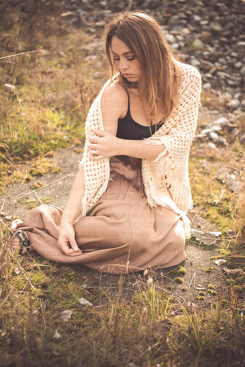 A beautiful  young woman with blonde hair sitting outside in the nature wearing a long skirt and a crochet stole