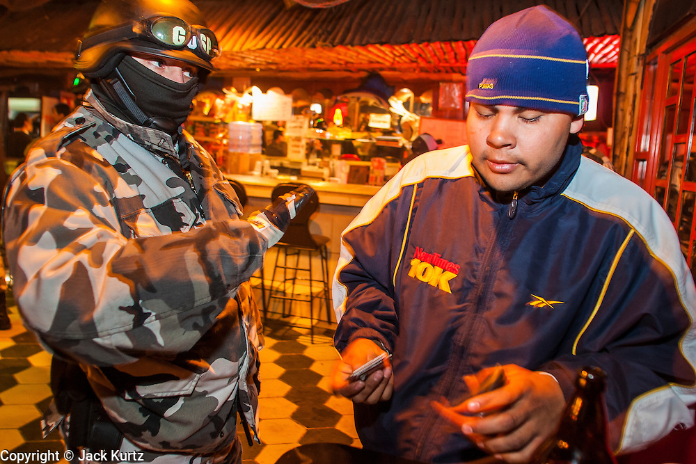 "05 FEBRUARY 2005 - NOGALES, SONORA, MEXICO: Nogales, Mexico, police talk to people in a bar in Nogales during an anti-gang sweep. Members of ""Grupo Operativos"" a special operations unit of the Nogales, Sonora, Mexico, police department, on patrol in Nogales, Saturday night, Feb. 5. The Operativos specialize in anti-gang enforcement and drug interdiction missions. In recent months they have stepped up patrol activity in Nogales communities near the border. In January 2005, the US Department of State has issued a travel advisory advising US citizens to avoid travel along the US Mexican border because of increased violence, including the kidnapping of US citizens, in border communities. Most of the violence has been linked to the drug cartels, who are increasingly powerful in Mexico. The Operativos also patrol the districts of Nogales frequented by US tourists in an effort to prevent crime directed against US citizens.   PHOTO BY JACK KURTZ"