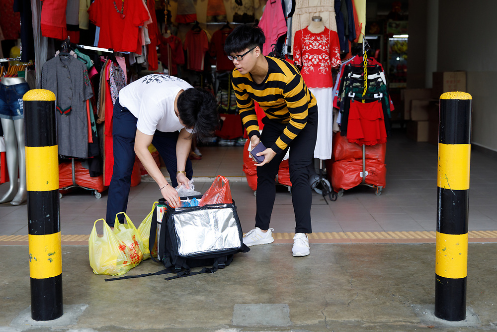 Customers pack their purchases into bags at Tiong Bahru Market, Singapore.