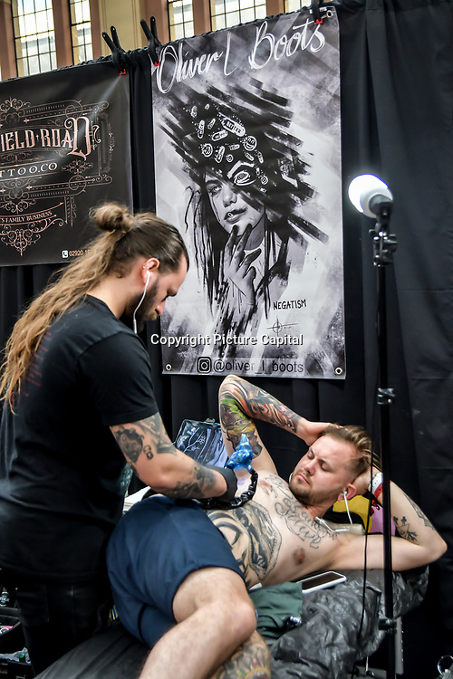 Olivia L Boots, tattoo a client at The Great British Tattoo Show, on 26 May 2019, London, UK.
