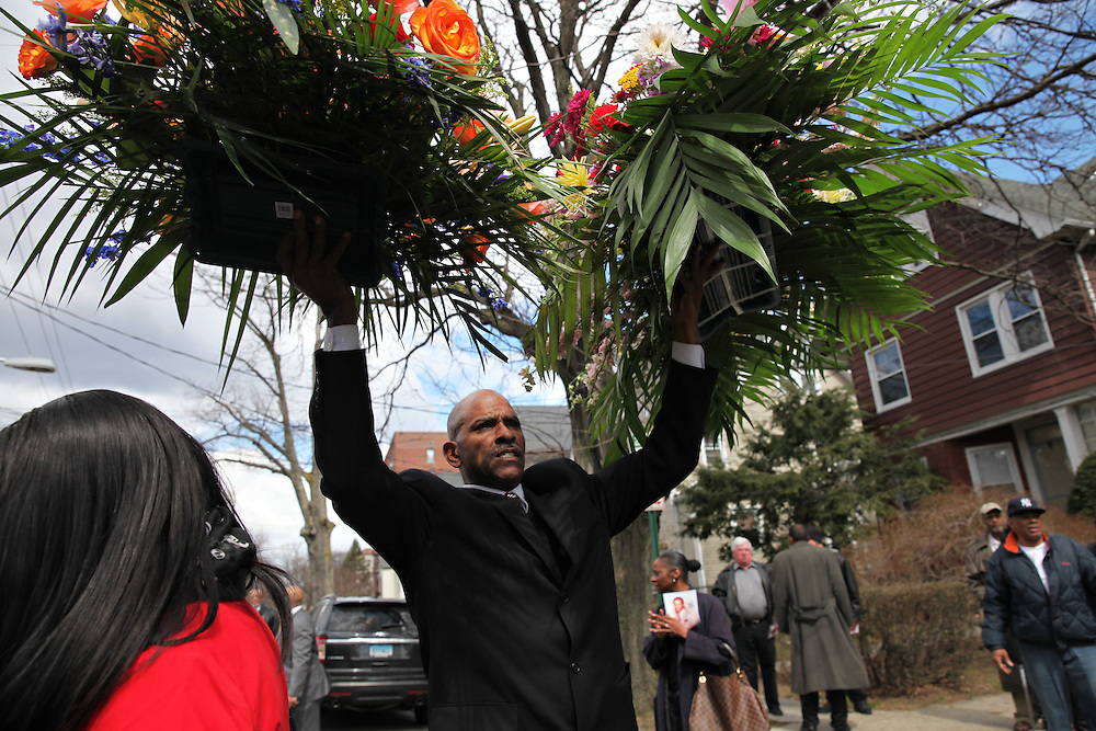 Funeral service member carries flowers after the service for former Knicks player Thomas Ray Williams, a Mount Vernon native, at Allen Memorial Church in Mount Vernon. (March 27, 2013)