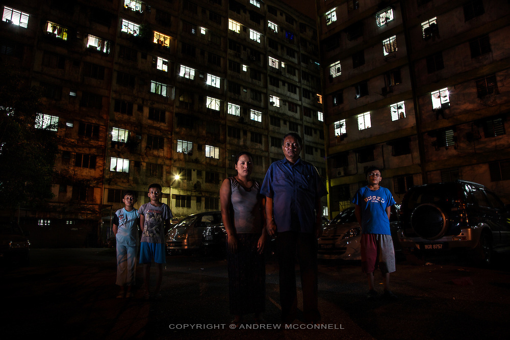 Daai Chin refugees from Burma, (L-R) Rose Pam, 10, Sho Hlai Ling, 12, Theing Mana, Pastor Bu Naing Ling, 58, and Shang Phu Lang Thang, 15, from Chin State, pictured outside their apartment block in Kuala Lumpur, Malaysia. <br /> <br /> &quot;Mindat is the capital town in the southern part of Chin State, from Mindat to my village, Makuiimnu,  takes 3 days and 2 nights walking.<br /> <br /> The southern part of Chin State is where Buddhism is spreading and many people are being lured to become Buddhists by the government. If they convert they are promised many things. I became a Christian in 1981 and started preaching the word of God. I traveled to all the villages and preached the gospel to the Chin people and I learned all about these things. I was banned from spreading the word of God and the church that I was building was stopped and I was threatened in many ways. They [ the government] stopped giving me the travel documents to travel around the villages. <br /> <br /> I had to report every night to the authorities, whenever I reported to the head of the locals I had to pay them. For me whenever I come across anyone I talk to them about the gospels, I don't care if they are Buddhists, I talk to everyone. Finally I was brought to the head of the town and forced to sign [a document] that I would stop preaching. I just signed this to please them but I kept on distributing leaflets and doing what I'm supposed to do, I'm not a politician and I don't do any politics.<br />  <br /> I was an evangelist and I did my best to spread the word of God. Buddhists and Catholics were giving villagers money to convert them, the competition was so intense that the Buddhist monk who was converting people planned to assassinate the Roman Catholic Father in Mindat; the man he paid a lot of money to assassinate the priest tried, but the gun misfired. <br /> <br /> Many of the preachers like me are forced to do labour and are interrogated many times and always have to report everywhere they go. This is very common and since I have been in those condit