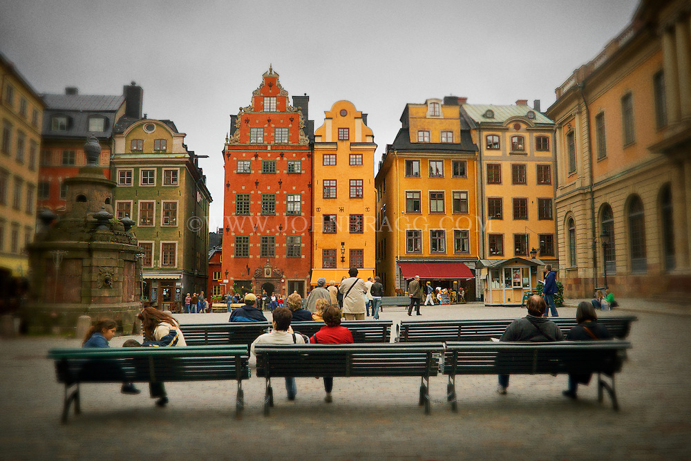 Colorful buildings line the Stortorget, or Old Square, in Stockholm, Sweden while people enjoy the scenery on benches