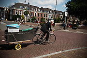 Jan van der Put fietst met een decorstuk voor een muziekvoorstelling naar de Stadsschouwburg in Utrecht.<br /> <br /> Jan van der Put is cycling with a scenery for a musical performance at the theatre
