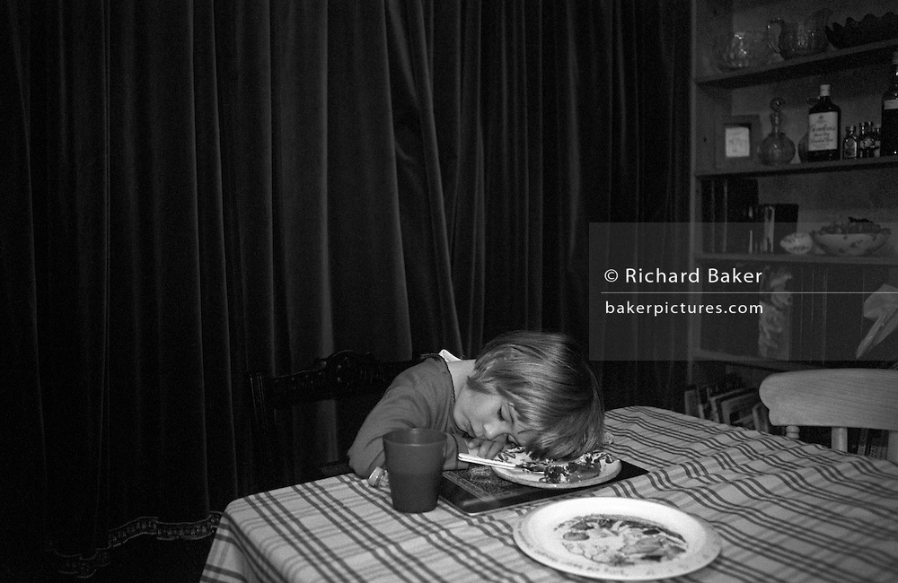 A 3 year-old girl falls asleep before finishing her dinner, the food of which is still on the plate under her head, at home in her south London home.