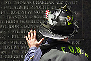 New York Fire fighter Stephen Saucedo of Ladder 13 puts his hand on the wall of names of fallen officers in the World Trade Center Plaza following the ceremony to end the recovery efforts at the WTC site. On his helmet is a photograph of his brother Gregory Saucedo of Ladder 5 who died during the WTC attack on 9/11 and whose body was never found.