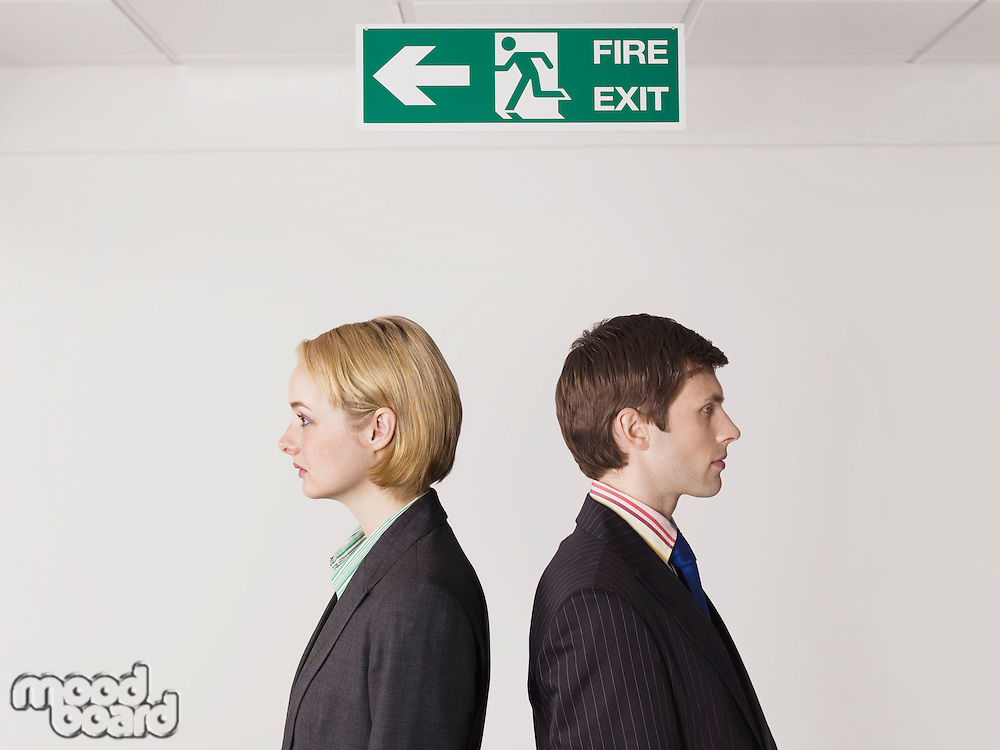 Business colleagues standing under exit sign