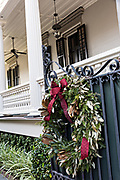 A historic home decorated for Christmas with a wreaths on King Street in Charleston, SC.