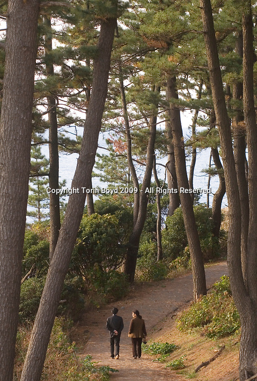 Nov. 27, 2009, Sakai City: This view shows an anonymous man from Nagoya, age 29, (on left) who was laid off from his job at an electronics maker and came to the Tojinbo cliffs in Fukui Prefecture with the intent of committing suicide. He is patrolling the cliffs of Tojinbo with Misako Kawagoshi (right), who herself lost her parents to suicide when she was a teenager. Ms. Kawagoshi is now partners with Yukio Shige, a 65 y/o retired policeman from Fukui Prefecture who founded the NPO Kokoro ni Hibiku Bunshu Henshukyoku in order to prevent suicides along the rocky cliffs at Tojinbo. This scenic tourist spot located on the Japan Sea coast in Sakai City, Fukui Prefecture has become a popular suicide spot, with twenty suicides occurring here in 2008 according to city officials. Shige took up his suicide prevention cause in 2004, just before retirement as a police deputy at a nearby police station where he was posted. When he discovered how many suicides were occurring here, he began patrolling the cliffs of Tojinbo in order to spot those contemplating suicide. Photo by Torin Boyd.