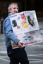 © Licensed to London News Pictures . 27/11/2015 . Salford , UK . A man carries cooking equipment from a branch of Tesco in Pendleton , Salford , this morning (Friday 27th November) as people behind queue for Black Friday offers . Last year (2014) scuffles and fights were reported amongst queuing bargain-hunters . Photo credit: Joel Goodman/LNP
