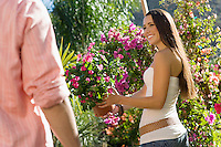 Woman Holding Flowering Plant in Garden