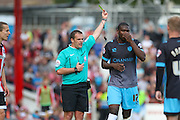 Referee Geoff Eltringham shows a yellow card to Sheffield Wednesday Defender Jeremy Helan during the Sky Bet Championship match between Brentford and Sheffield Wednesday at Griffin Park, London, England on 26 September 2015. Photo by Phil Duncan.